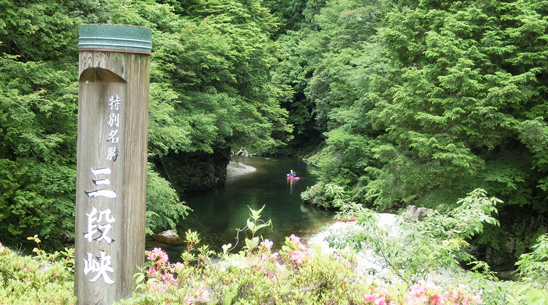 三段峡の看板と、渓谷の中でボートを漕ぐ人